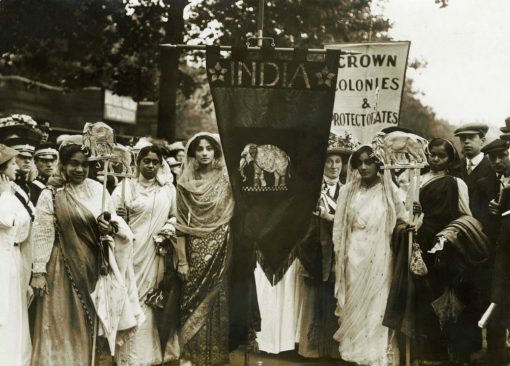 Photograph of Indian suffragettes on the Women's Coronation Procession, 17 June 1911. To mark the coronation of King George V, a huge march through London was arranged demanding votes for women in Coronation year. Led by suffragettes dressed as powerful women from the past, the march of 40,000 women was watched by crowds, some on specially erected stands. Indian suffragettes, including Mrs Roy, Mrs Mukerjea and Mrs Bhola Nauth marched in the Empire Pageant section of the procession along with representatives from New Zealand, South Africa and the West Indies.